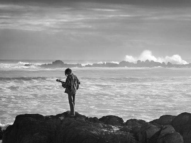 海辺でバラードを歌う男性