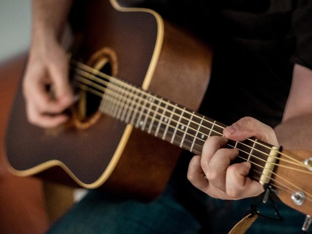 趣味でギターを弾いている男性